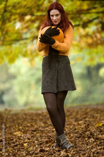 A young woman holding a pumpkin