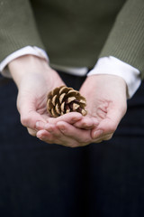 A young woman holding a pine cone