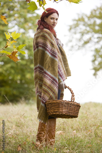 A young woman wrapped in a blanket, holding a wicker basket