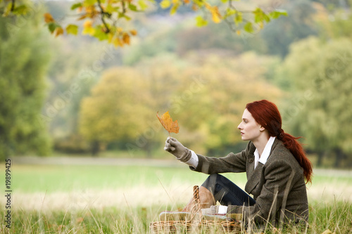 A young woman sitting in the grass, looking at a leaf