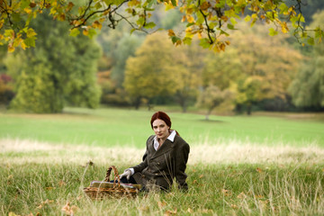 A young woman sitting in the grass with a wicker basket