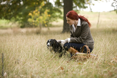 A young woman in a field stroking her dog
