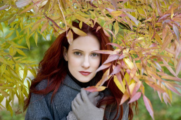 A young woman standing under a tree in autumn time