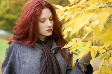 A young woman looking at autumn leaves