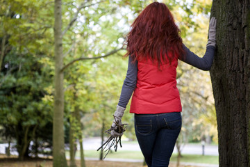The back view of a young woman holding a handful of twigs