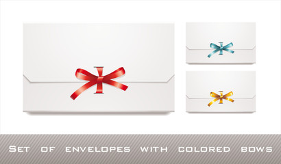 set of white envelopes with colored bows