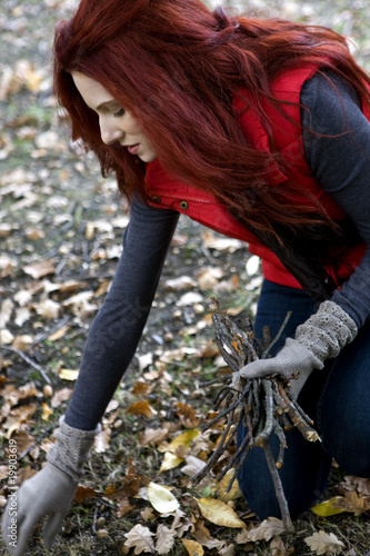 A young woman gathering twigs in autumn time