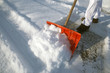 Leinwandbild Motiv shoveling snow with an orange snow shovel