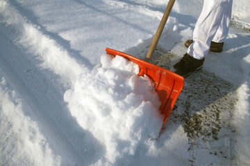 shoveling snow with an orange snow shovel