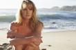 Naked model posing on a beach