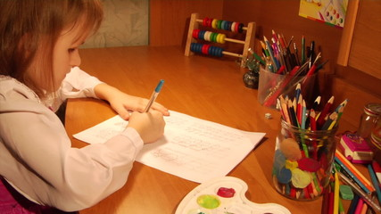 little girl writing elementary homework