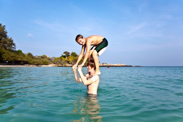 brothers are playing together jumping from shoulder into the sea