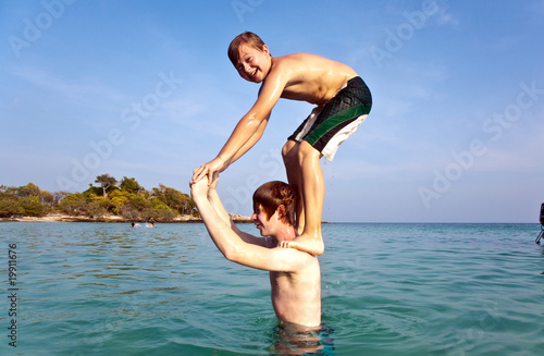 brothers are playing jumping from shoulder into the sea