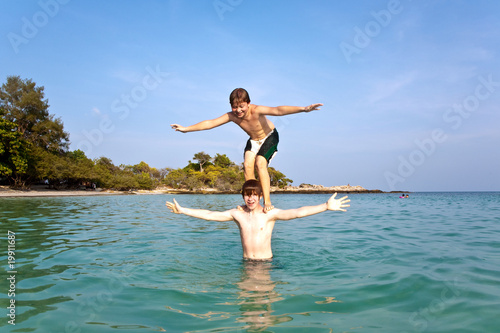 brothers are playing together pickaback  in a beautiful sea