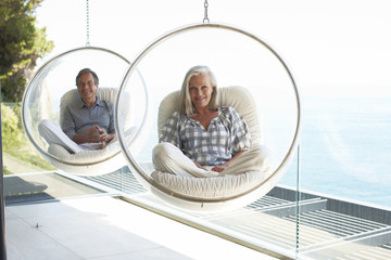 Mature couple sitting on designer chairs