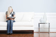 Young Woman Sitting on Sofa Reading