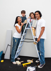 Happy young family renovating a room