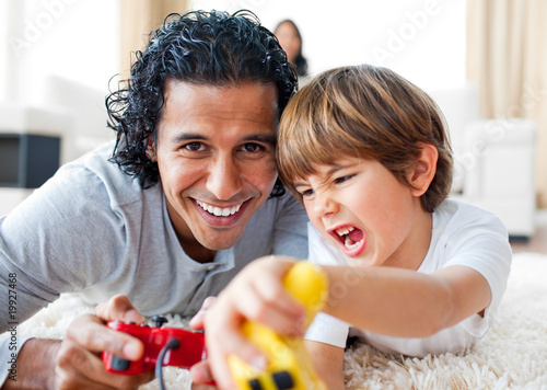 Excited little boy and his father playing video games lying on t