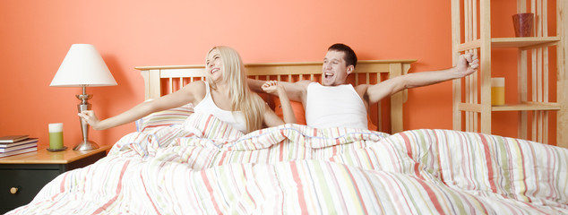 Young Couple Lying in Bed Stretching