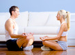 Young Couple Sitting on Floor Meditating