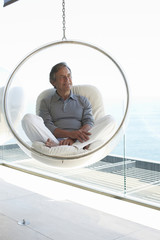 Mature man sitting on a design chair