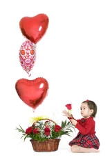 Cute baby girl holding a bunch of heart-shaped balloons