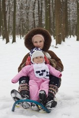 cute baby girl and her older sister sledding