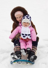 cute baby girl and her older sister sledding