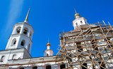 Russian Orthodox Church under construction against blue sky.