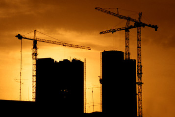 building construction with cranes and back lit by setting sun