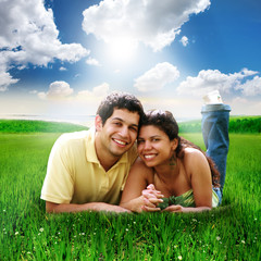 Happy Couple Laying Down in a Green Field