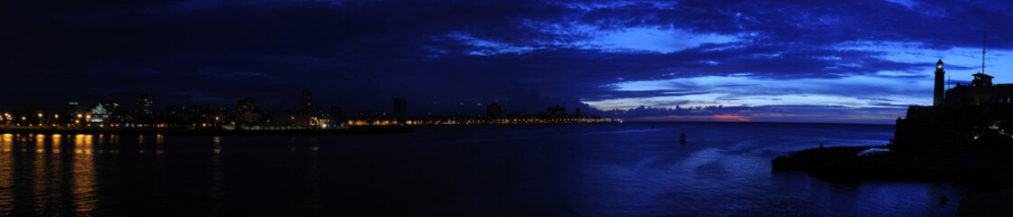 """Panoramic view of El """"Morro"""" lighthouse and havana bay at dusk"""