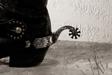 Cowboy boots with spurs on the wooden desk
