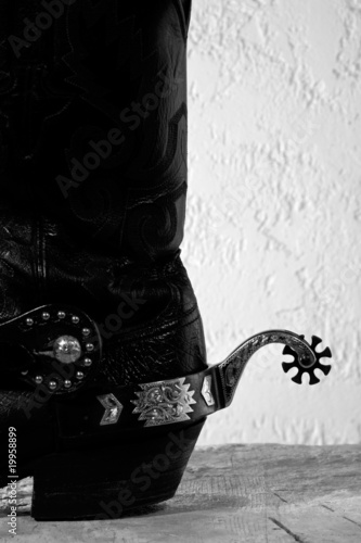 Aluminium Retro Cowboy boots with spurs on the wooden desk