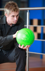 Portrait of young man preparing to play bowling
