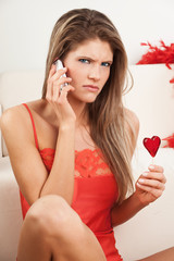 Young woman in red angry at the phone call
