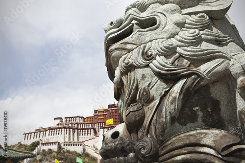 tibet: tone lion at the gate of potala palace