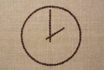 Time concept. Clock made of fried coffee beans on grunge canvas