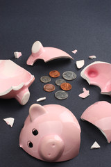 Broken piggy bank containing few coins.