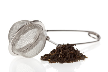 Tea infuser with Green Tea leaves isolated on a white background