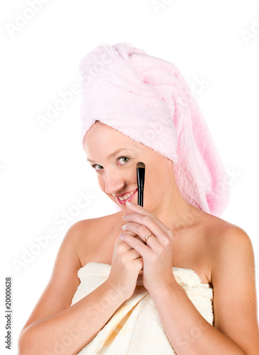 Pretty woman applying make up with white towel on her head