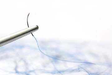 Surgical suture on needle holder