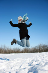 Happy jumping woman in the snowy forest