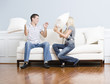 Young Couple Having a Pillow Fight on Sofa
