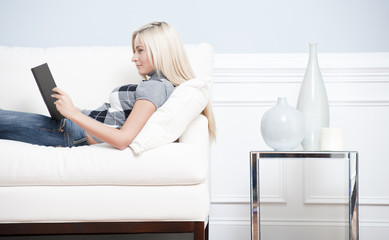 Woman Reclining on Couch With a Book