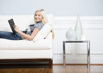 Smiling Woman Reclining on Couch With a Book