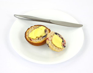 Buttered berry muffin on plate with knife