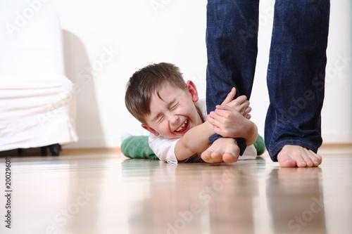 Kind weint und hält sich am Bein der Mutter fest schreit - 20029608