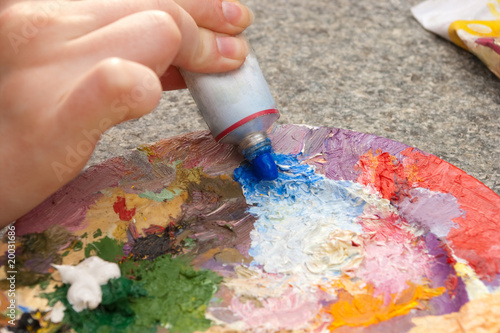 close-up of hand squeezing blue oilpaint on palette