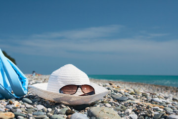 Hat with sunglasses on the pebbles